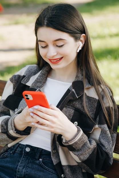 Молодая красивая женщина, стоя на скамейке с помощью телефона Premium Фотографии