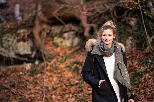 아름 다운 젊은 여자는 단풍 숲에 서있다. 겨울 옷은 추위로부터 보호합니다. 무료 사진