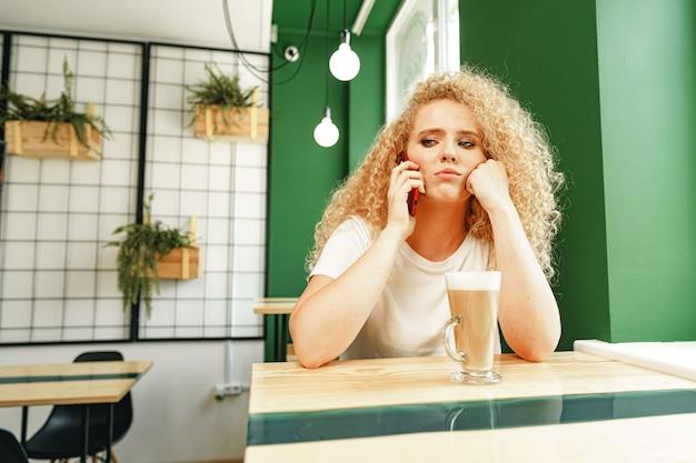 Молодая красивая женщина разговаривает по телефону в кафе Premium Фотографии