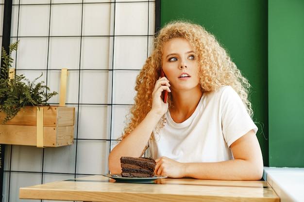 Молодая красивая женщина разговаривает по телефону в кафетерии Premium Фотографии