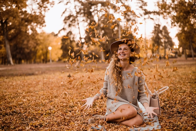 Young beautiful woman throwing the yellow leafs in the air. Premium Photo