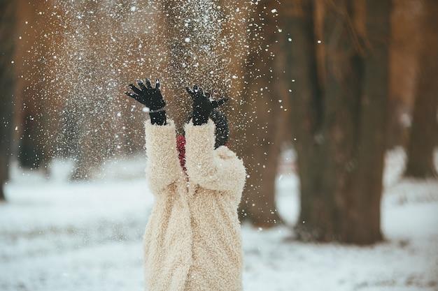 La giovane bella donna getta la neve sopra la testa Foto Gratuite