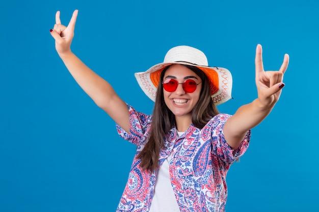 Шляпа лета молодого красивого туриста женщины нося и красные солнечные очки смотря радостный делающ символы утеса жизнерадостно усмехаясь и позитв над голубой стеной Бесплатные Фотографии