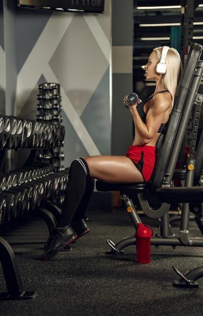 ジムでトレーニングしている若い美しい女性。フィットネス、トレーニング、スポーツ、健康の概念 無料写真