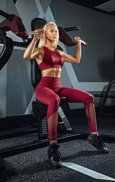 Молодая красивая женщина тренируется в тренажерном зале. концепция фитнеса, тренировки, спорта, здоровья Бесплатные Фотографии