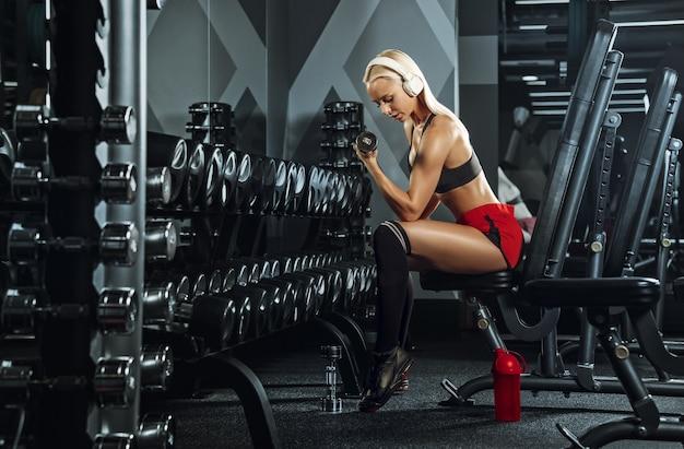 체육관에서 훈련하는 젊은 아름 다운 여자. 피트니스, 운동, 스포츠, 건강의 개념 무료 사진