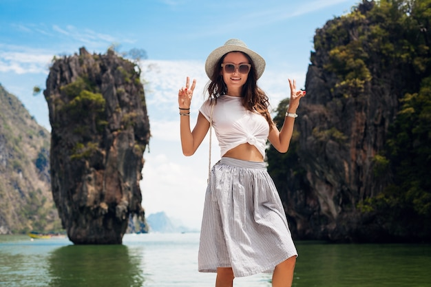 Young beautiful woman traveling in thailand, summer vacation, casual style, sunglasses, hat, cotton skirt, t-shirt, smiling, happy, adventures Free Photo