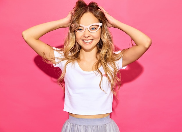 Young beautiful woman . trendy woman in casual summer clothes in fake props sunglasses. positive female emotion facial expression body language. funny model playing with her hair on pi Free Photo