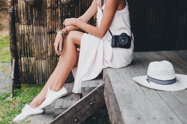 Young beautiful woman on tropical vacation in asia, summer style, white boho dress, sneakers, digital photo camera, traveler, straw hat, legs close up details Free Photo