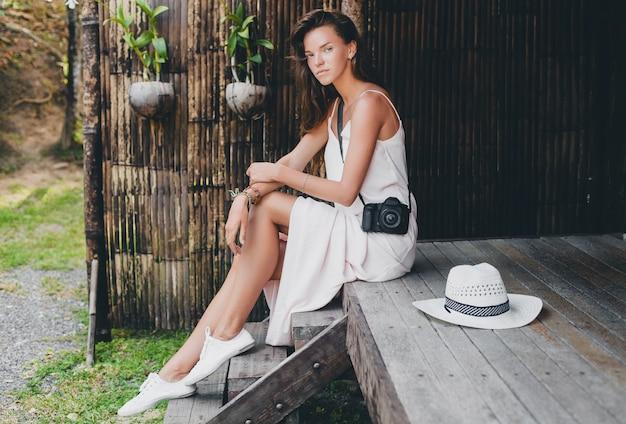 Giovane bella donna in vacanza tropicale in asia, stile estivo, abito boho bianco, scarpe da ginnastica, fotocamera digitale, viaggiatore, cappello di paglia, sorridente, boho Foto Gratuite
