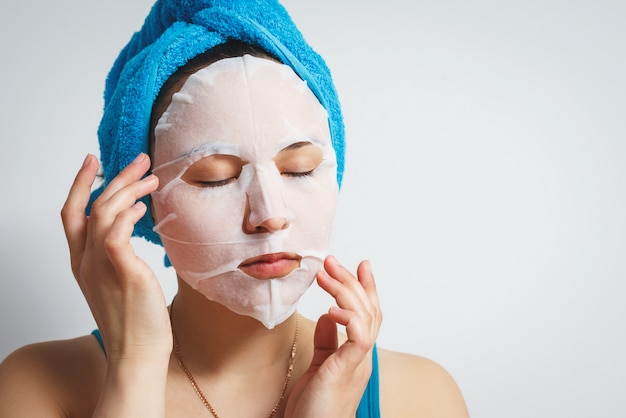 A young beautiful woman uses a moisturizing cosmetic fabric face mask with a towel wrapped around her head. on white wall. Premium Photo