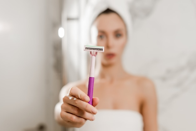 Young beautiful woman uses razor blade for bikini wrapped in towels in the bathroom, razor in focus Premium Photo