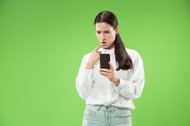 녹색 배경에 스튜디오에서 휴대 전화를 사용 하여 젊은 아름 다운 여자. 인간의 얼굴 감정 개념. 무료 사진