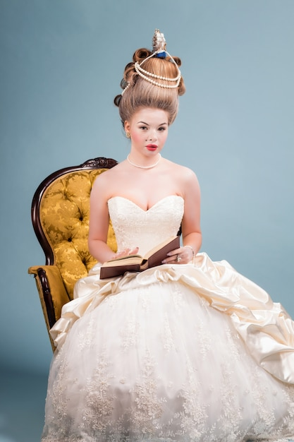 Young beautiful woman in vintage victorian dress with complicated hairstyle sitting in a chair Premium Photo