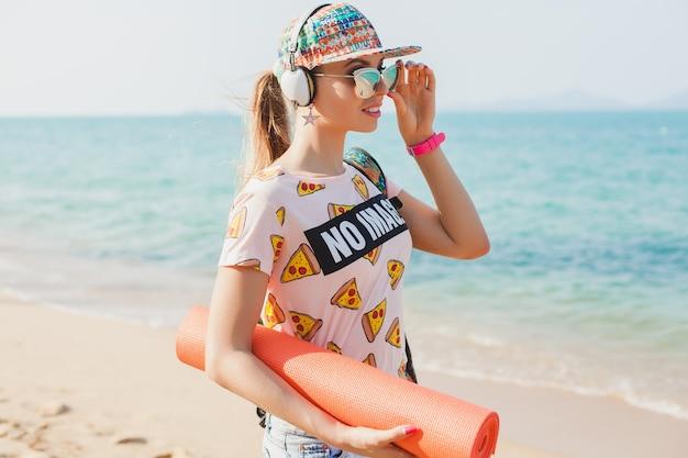 Giovane bella donna che cammina sulla spiaggia con materassino yoga, ascoltando musica in cuffia, stile malloppo sportivo hipster, pantaloncini di jeans, t-shirt, zaino, berretto, occhiali da sole, soleggiato, weekend estivo, allegro Foto Gratuite
