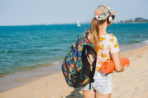 ヨガマット、流行に敏感なスポーツ盗品スタイル、デニムのショートパンツ、tシャツ、バックパック、晴れ、夏の週末を保持してビーチを歩く若い美しい女性 無料写真
