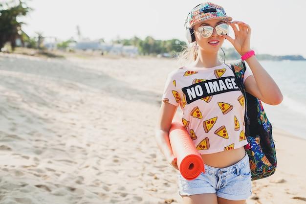 ヨガマットとビーチを歩いて、ヘッドフォンで音楽を聴いて、流行に敏感なスポーツ盗品スタイル、デニムのショートパンツ、tシャツ、バックパック、キャップ、サングラス、晴れ、夏の週末、陽気な若い美しい女性 無料写真