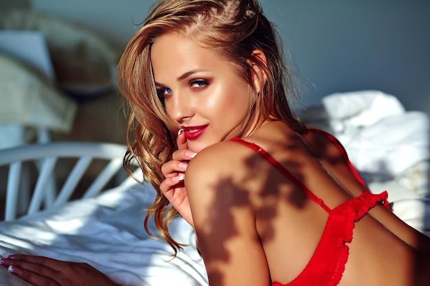 朝ベッドに赤いランジェリーを着ている若い美しい女性 無料写真