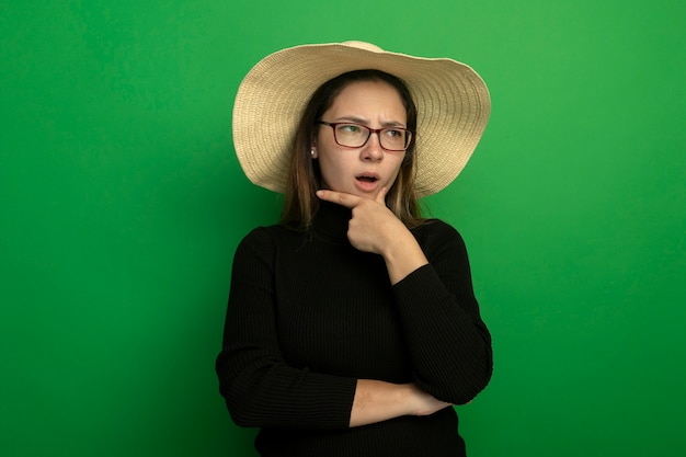 Young beautiful woman wearing summer hat in a black turtleneck and glasses looking aside with hand on chin being confused standing over green wall Free Photo