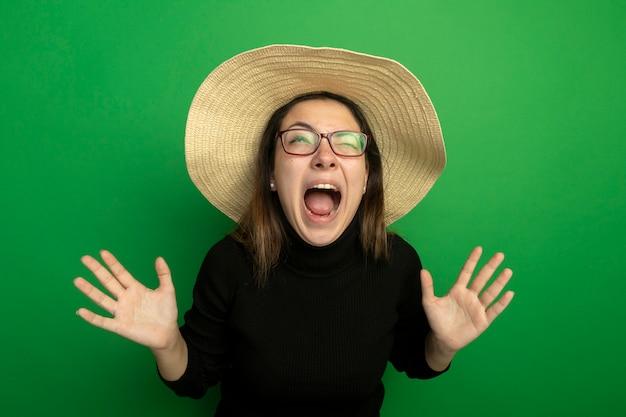 Giovane bella donna che indossa un cappello estivo in un dolcevita nero e occhiali che grida con le mani alzate in piedi sopra la parete verde Foto Gratuite