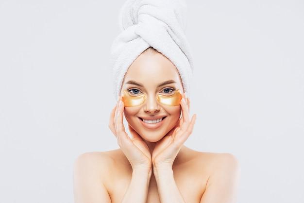 頭にタオルを持つ若い美しい女性 Premium写真