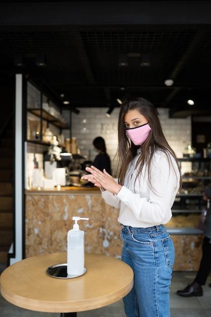 Giovane bella donna con un sorriso attraente in maschera protettiva utilizzando gel disinfettante per le mani per lavarsi le mani. la ragazza si trova sulla soglia fuori nella scena del caffè. concetto di prevenzione del coronavirus. Foto Gratuite