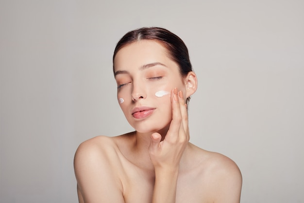 Young beautiful woman with closed eyes is applying cosmetic cream on her face. cream on the cheeks.skin care. dry skin. beauty concept. Premium Photo