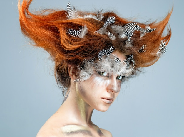 Young beautiful woman with complicated avant-garde hairstyle ...