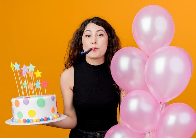 생일 케이크와 오렌지 벽 위에 서 휘파람 행복하고 흥분 생일 파티 개념을 불고 공기 풍선의 무리를 들고 곱슬 머리를 가진 젊은 아름 다운 여자 무료 사진