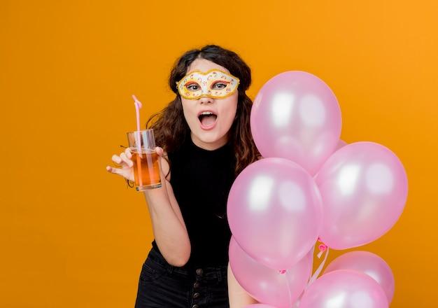 오렌지를 통해 파티 마스크 행복하고 쾌활한 생일 파티 개념에 공기 풍선의 무리와 칵테일을 들고 곱슬 머리를 가진 젊은 아름 다운 여자 무료 사진
