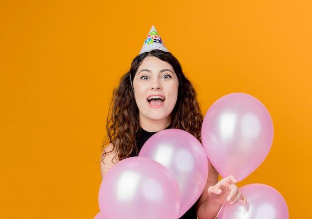 Giovane bella donna con i capelli ricci in una protezione di vacanza che tiene gli aerostati di aria happyand eccitato concetto di festa di compleanno in piedi sopra la parete arancione Foto Gratuite