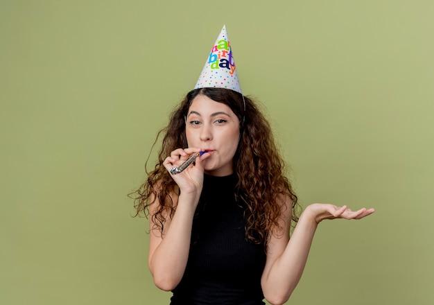 明るい壁の上に立っている誕生日パーティーのコンセプトを腕で口笛を吹くホリデーキャップで巻き毛の若い美しい女性 無料写真