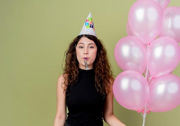 明るい壁の上に立っている誕生日パーティーを祝う幸せで前向きな笛を吹く気球を保持している休日の帽子の巻き毛の若い美しい女性 無料写真