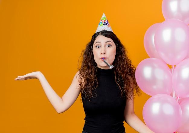 오렌지 벽 위에 서있는 측면 생일 파티 개념에 팔을 확산 고백 찾고 휘파람을 불고 공기 풍선을 들고 휴가 모자에 곱슬 머리를 가진 젊은 아름 다운 여자 무료 사진