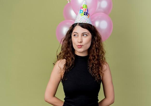 明るい壁の上に立って幸せで前向きな誕生日パーティーのコンセプトを脇に見て気球を保持しているホリデーキャップで巻き毛の若い美しい女性 無料写真