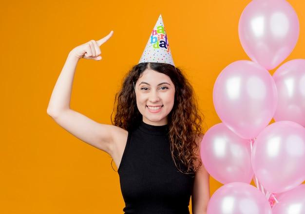 オレンジ色の壁の上に立っている人差し指幸せでポジティブな笑顔の誕生日パーティーのコンセプトを示す気球を保持しているホリデーキャップで巻き毛の若い美しい女性 無料写真