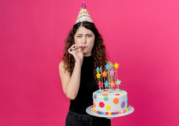 생일 케이크를 들고 휴가 모자에 곱슬 머리를 가진 젊은 아름 다운 여자 핑크 벽 위에 서 행복하고 긍정적 인 생일 파티 개념 호각을 불고 무료 사진