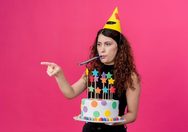 분홍색 벽 위에 서있는 불쾌한 생일 파티 개념을 찾고 측면에 손가락으로 가리키는 휘파람을 불고 생일 케이크를 들고 휴가 모자에 곱슬 머리를 가진 젊은 아름 다운 여자 무료 사진