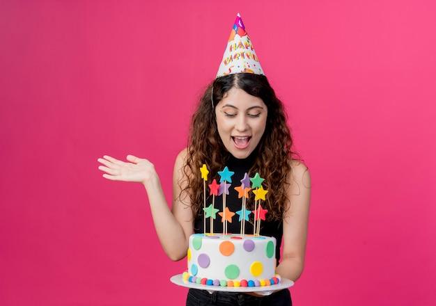 ピンクの壁の上に立っている誕生日ケーキ幸せで興奮した誕生日パーティーのコンセプトを保持しているホリデーキャップの巻き毛の若い美しい女性 無料写真