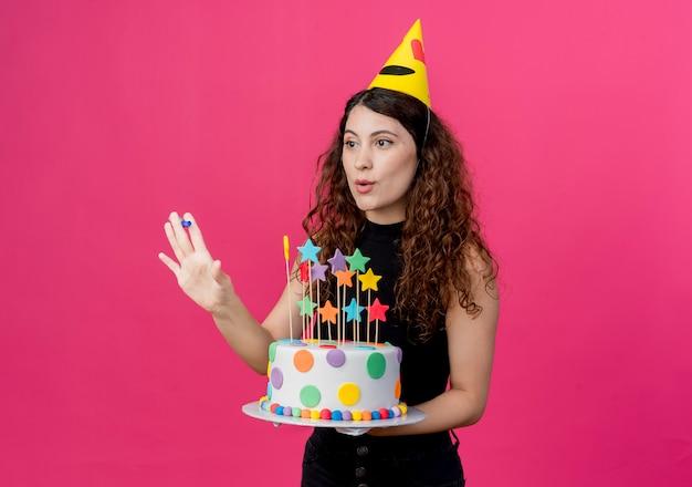 ピンクの壁の上に立っている誕生日ケーキ幸せでポジティブな誕生日パーティーのコンセプトを保持しているホリデーキャップで巻き毛の若い美しい女性 無料写真