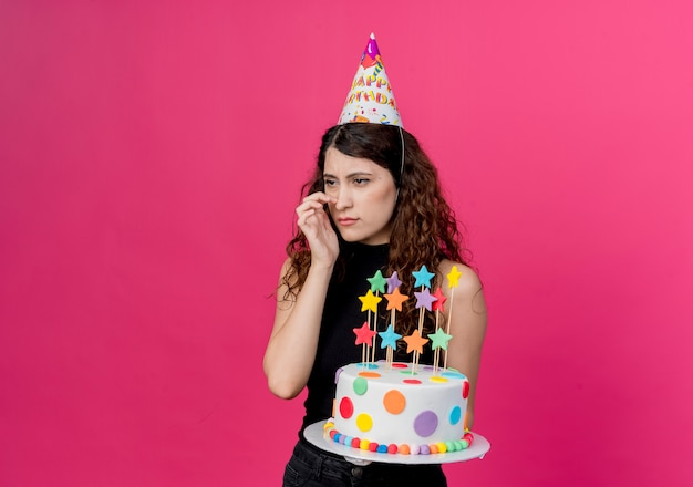 ピンクの壁の上に立っている混乱した誕生日パーティーのコンセプトを脇に見てバースデーケーキを保持しているホリデーキャップの巻き毛の若い美しい女性 無料写真