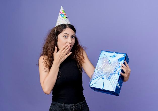 青い壁の上に立っている驚きの誕生日パーティーのコンセプトを探している誕生日プレゼントボックスを保持しているホリデーキャップで巻き毛の若い美しい女性 無料写真
