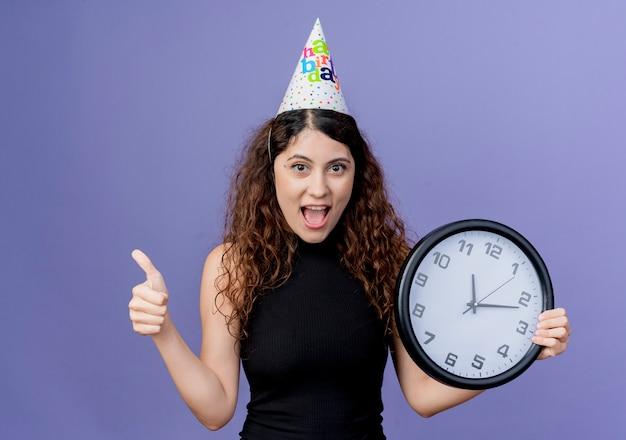 青い壁の上に立っている誕生日パーティーのコンセプトを元気に親指を示して笑顔の壁時計を保持している休日の帽子の巻き毛の若い美しい女性 無料写真