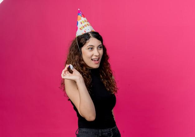 핑크 벽 위에 서 휘파람 행복하고 긍정적 인 생일 파티 개념을 들고 휴가 모자에 곱슬 머리를 가진 젊은 아름 다운 여자 무료 사진