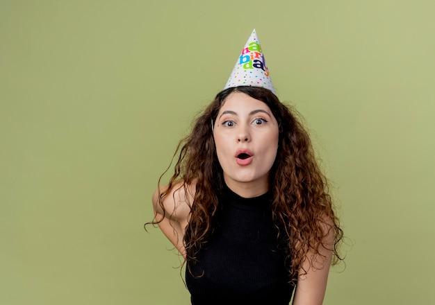 明るい壁の上に立っている休日の帽子の巻き毛の若い美しい女性は誕生日パーティーのコンセプトを驚かせた 無料写真