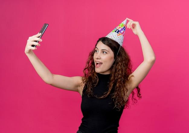ピンクの上の誕生日パーティーのコンセプトを元気に笑顔で自分撮りを取っているホリデーキャップの巻き毛の若い美しい女性 無料写真
