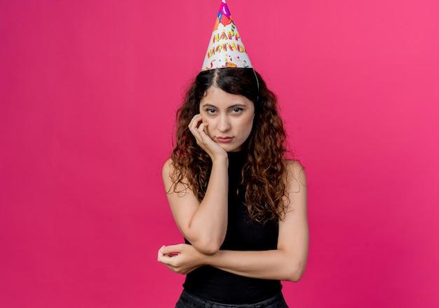 핑크를 통해 얼굴 생일 파티 개념에 슬픈 표정으로 휴가 모자에 곱슬 머리를 가진 젊은 아름 다운 여자 무료 사진