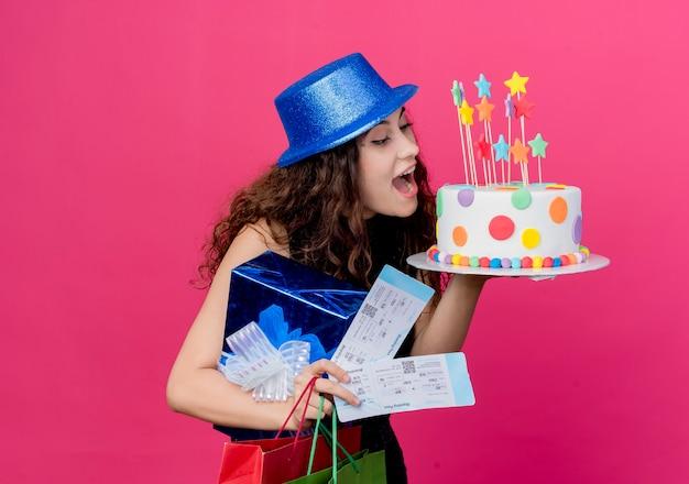 ピンクの壁の上に立っている誕生日ケーキのギフトボックスと航空券幸せで興奮した誕生日パーティーのコンセプトを保持している休日の帽子で巻き毛の若い美しい女性 無料写真