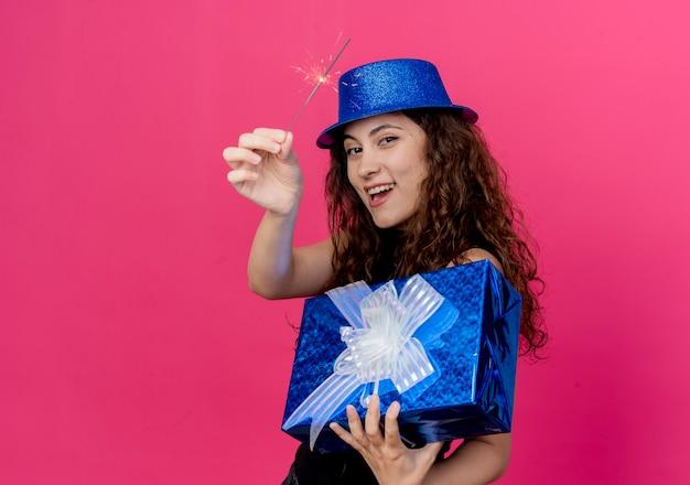 분홍색 벽 위에 서 생일 선물 상자와 향 행복하고 쾌활한 생일 파티 개념을 들고 휴가 모자에 곱슬 머리를 가진 젊은 아름 다운 여자 무료 사진