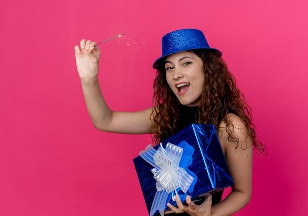 ピンクの上の誕生日プレゼントボックスと線香花火幸せで興奮した誕生日パーティーのコンセプトを保持している休日の帽子の巻き毛の若い美しい女性 無料写真